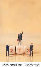 Miniature people: businessman standing on wooden podium using as background (Financial and Business competition concept)