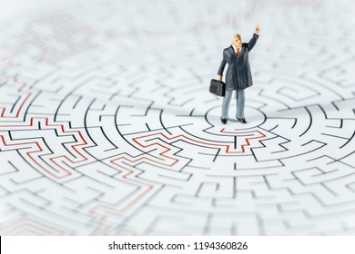 Miniature people Businessman standing on center of maze using