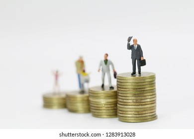 Miniature people, businessman standing on stack of coins. Investment and business concept