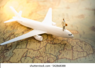 Miniature people : businessman standing  on airplane for travel around the world, using as business trip traveler adviser agency or explorer on earth background concept.