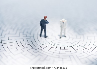 Miniature people: Businessman standing on center of maze using as background business finding solution, problem solving and challenge concept.