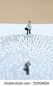 Miniature people: Businessman standing on start point of maze using as background business finding solution, problem solving and challenge concept.