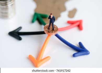 Miniature people: Businessman standing on coins and  arrow pathway choice using as Business decision concept.