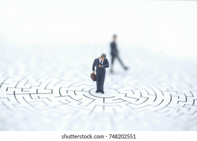 Miniature people: Businessman standing on center of maze Concepts of finding a solution, problem solving and challenge