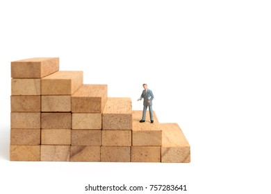 Miniature people: Businessman standing on wood block isolated on white background