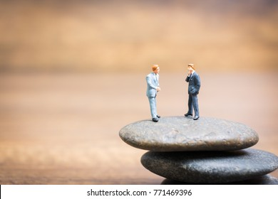 Miniature people : Businessman standing on stone , Challenges and risks Concept