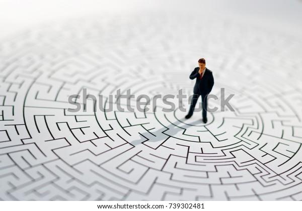 ミニチュアの人:迷路の真ん中に立つ実業家。解決策を見つけ、問題を解決し、課題を解決するコンセプト。