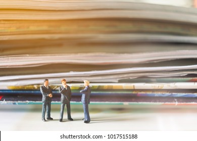 Miniature people: Businessman standing and stack of book with warm lighting background