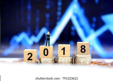 Miniature people : businessman standing with  stock market number and wooden block 2018 background,Concept of financial stock market.