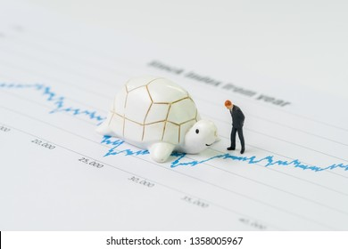 Miniature people businessman standing with turtle or tortoise on rising growth stock market value price graph and chart, slow invest but steady for long term success, VI or value investment concept.