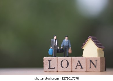 Miniature people businessman standing with wood word LOAN and blurred green nature as background. Trading house concept