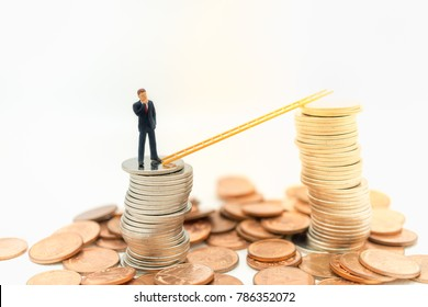 Miniature people: Businessman thinking and standing on  stack of coins with stair using as background money growth up, saving, financial, business concept.