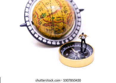 Miniature people :  businessman and Tie blowing in wind stand on gold coins and compass, business  and travel concept.