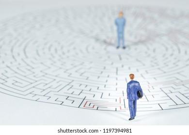 Miniature people Businessman Walking into a maze.