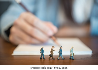 Miniature people: Businessmen go through the women who are writing the book.