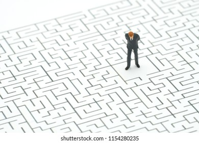 Miniature people businessmen standing in the center of the maze. Business Idea Concepts Troubleshooting Analysis of problems to find solutions.
