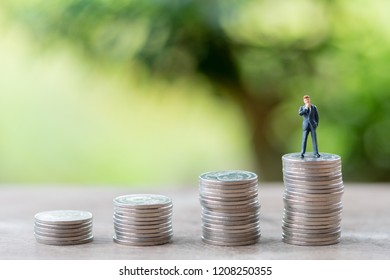 Miniature people businessmen standing Investment Analysis Or investment stack of coins to thinking and planning.as background business concept with copy space.