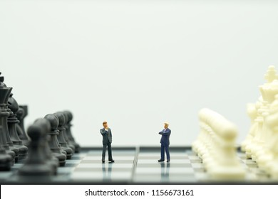 Miniature people businessmen standing on a chessboard with a chess piece on the back Negotiating in business. as background business concept and strategy concept with copy space.