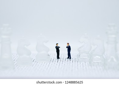 Miniature people businessmen standing on a chessboard. picture user for background business concept and strategy concept with copy space.