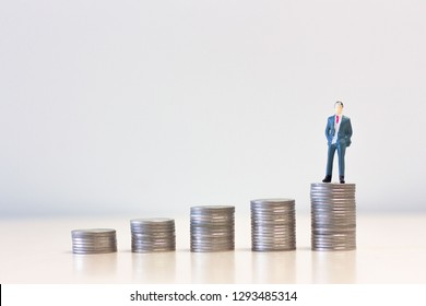 Miniature people businessmen standing on top of stack of coins. Business Concept.