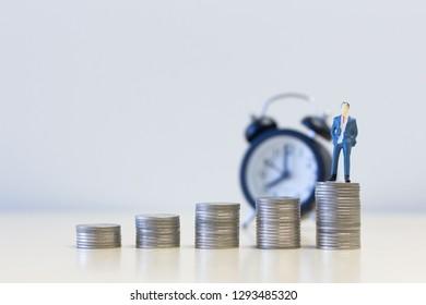Miniature people businessmen standing on Money coins stack . Money and financial concepts. finance sustainable development . economic growth.