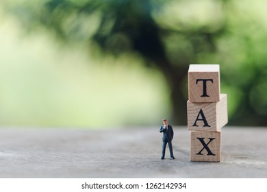 Miniature people businessmen standing with wood word TAX using as background business concept and finance concept with copy space  for your text or  design.