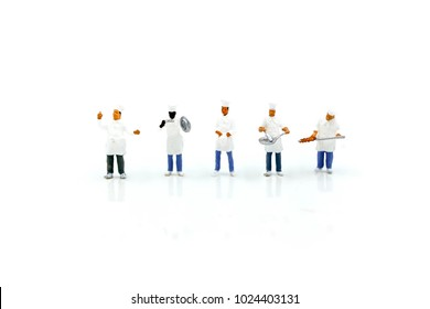 Miniature people : Chef during cooking and working on white background.