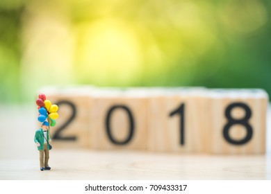 Miniature people children with balloons celebrating new year eve on 2018 text wooden block