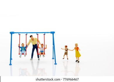 Miniature people, children and family enjoy with swing , happy family day concept.