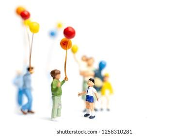Miniature people : Children holding balloon on white background