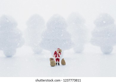Miniature people in Christmas Theme. Santa Claus giving Christmas gift to children on Christmas day
