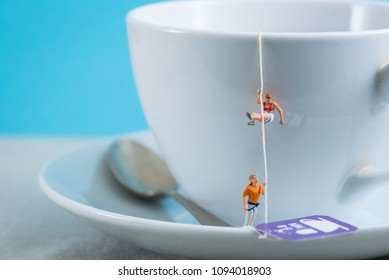 Miniature people climbig up to a cup of tea