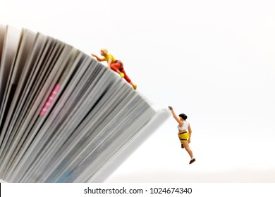 Miniature people climbing book with challenging route on cliff, Concept of the path to purpose and success.