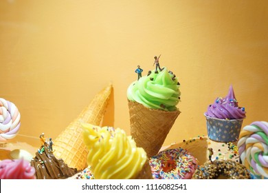 Miniature people climbing the giant ice cream