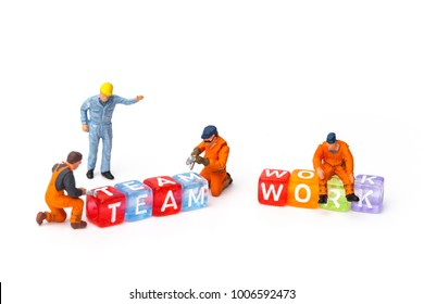 """Miniature people. The concept of a collective solution to any problem. Miniature toy workers build the letter """"TEAMWORK"""". Close-up view."""