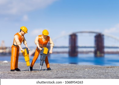 Miniature people. The concept of a collective solution to any problem. Miniature toy workers drilling concrete driveway with jackhammer. Close-up view.