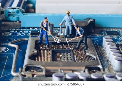 Miniature people concept idea : worker mining computer mainboard bitcoin electronic currency