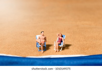miniature people couple wearing swimsuit sitting on the lounge chair at beach