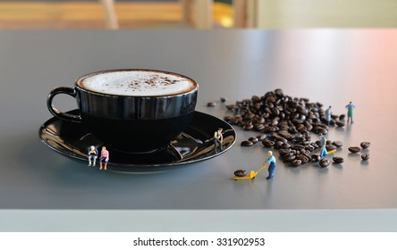 Miniature people with a cup of coffee and coffee bean
