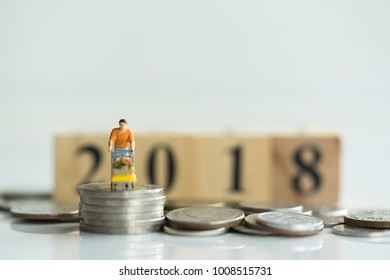 Miniature people, customer with shopping carts on coins stack and 2018 wooden block as backdrop. Concept of money saving, financial.
