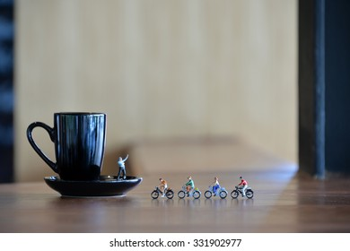 Miniature people cycling to a cup of coffee