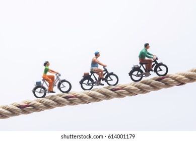 Miniature people cycling on rope