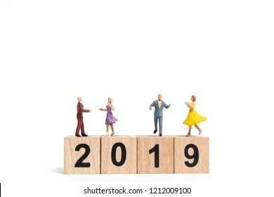 Miniature people dancing on wooden block number 2019. on white background