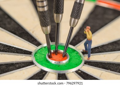 miniature people with dart in bull's eye, close up concept
