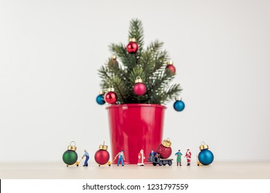 Miniature people decorating giant Christmas tree.