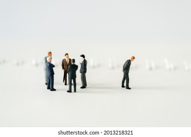 Miniature people A depressed Businessman mini figures standing out of group thinking on white background using as Success Business partnership development and Commerce Strategy Planning concepts