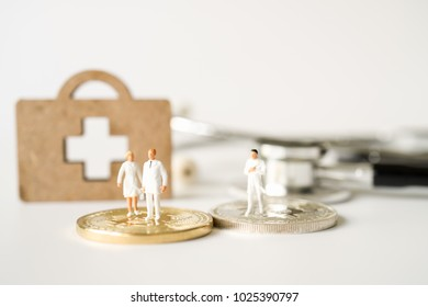 Miniature people, Doctor and Nurse emergency medical team stand on gold bitcoin background. Health care, life insurance travel hospitality and bitcoins block chain technology concept.