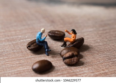 Miniature people drinking coffee on giant beans. Coffee date, break or business meeting, Taking time for conversation and a hot beverage.