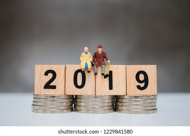 Miniature people, elderly people sitting on wooden year 2019 and stack coins using as job retirement and business concept