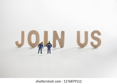 Miniature people: Engineer standing infront to seeing on JOIN US word use asbusiness concept.